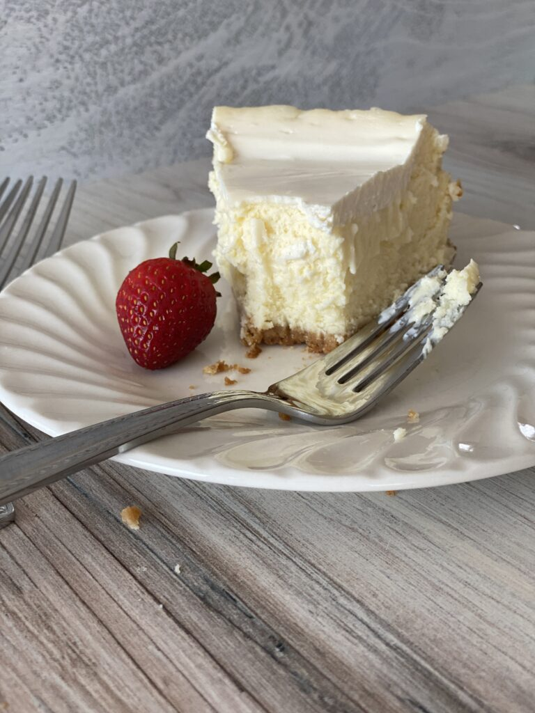 a bite from a creamy cheesecake slice