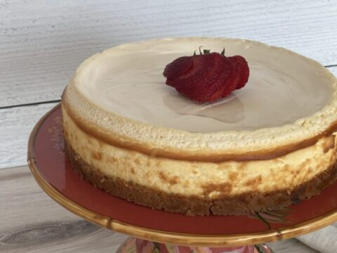 Creamy cheesecake on a platter with a strawberry garnish